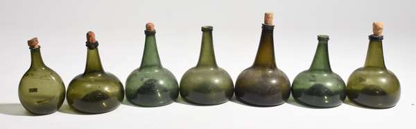 "Seven green glass onion bottles, 6.5-8""H."