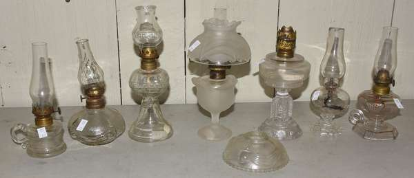Seven clear glass miniature lamps (23-111)
