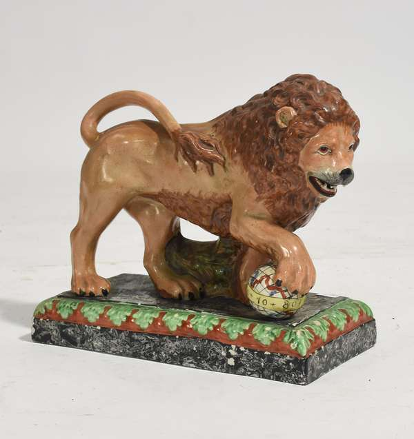 """Early Staffordshire pearlware lion figurine with globe under paw, 10.5""""L. x 5""""W. x 9.5""""H.(tail repaired)"""