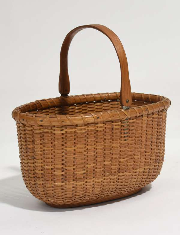 """Oval Nantucket basket with swing handle, 9.35""""L. x 6""""W. x 5.25""""H."""