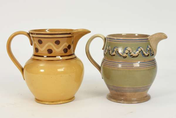 """Two mocha pouring pitchers, 7"""" earthworm example with a 7.5"""" yellow ware example"""