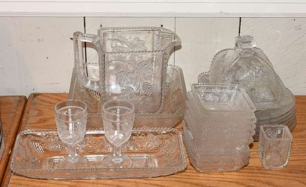 Lot of clear patterned glass, including butter dish, pitcher, plates, etc., 23 pieces (5-409)