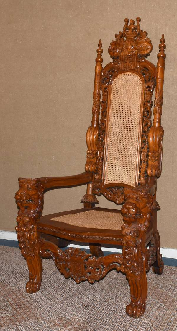 "Impressive carved king's chair with caned seat and back, with lion and armorial carvings, 69""H. (105-12)"