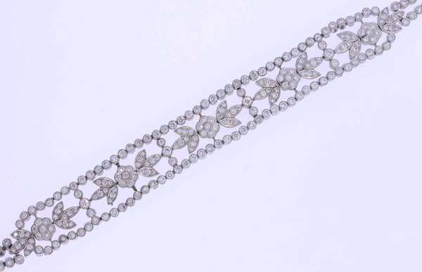 Pretty diamond and platinum (tested) bracelet with floral motif set with approximately 7.0 ct. tw. round brilliant cut diamonds, H-I color, VS-SI clarity, very good cut. The bracelet measures ½ inch wide and is 7 inches long. 39.3 grams. Good condition.