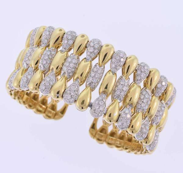Impressive wide eighteen karat (tested) yellow gold cuff bracelet set with approximately 8.0 ct. tw. round brilliant cut diamonds, F-G color, VS clarity, very good cut. The bracelet measures 1 1/8 inches wide with a 6 inch inner diameter. 128.0 grams. Very good condition.