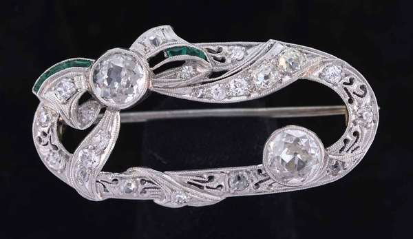 Sweet Art Deco style platinum pin (14K white gold pin stem) with ribbon and bow swirls around two Old European cut diamonds each approximately .70 ct., K-L color, VS-VVS clarity, fair-good cut, accented by approximately .60 ct. tw. Old European, Old Mine and single cut side diamonds, H-L color, VS-SI clarity. Accented by small calibre cut synthetic emeralds (one is missing). It measures 1 ½ by ¾ inches. 6.8 grams. Slightly worn due to missing syn. emerald. otherwise good condition.