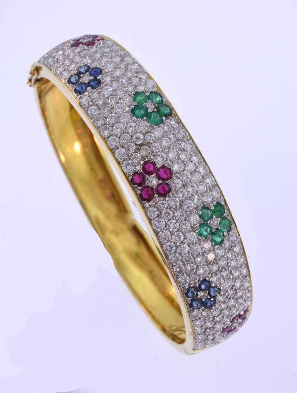 Floral pattern pave set 18K yellow gold bangle bracelet with hinge closure set with approximately 7.0 ct. tw. round brilliant cut diamonds, F-G color, VS clarity,  2.0 ct. tw. medium-medium light slightly greenish blue emeralds, medium dark rubies and medium blue sapphires. It measures 5/8 inches wide, inner diameter 6 ¼ inches. 41.6 grams. Very good condition.