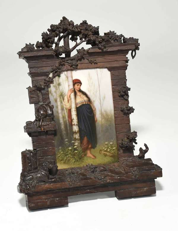 "KPM plaque of woman with tambourine in woods, with carved Black Forest frame, with dog and trees; tree in plaque extending into frame. Sight size of plaque: 9"" x 6"". Frame 13.25""W x 17""H. 3.5 lbs. Condition: not examined out of frame. Crack to top of frame. Some losses to frame, in horn on left, tips of leaves, etc."