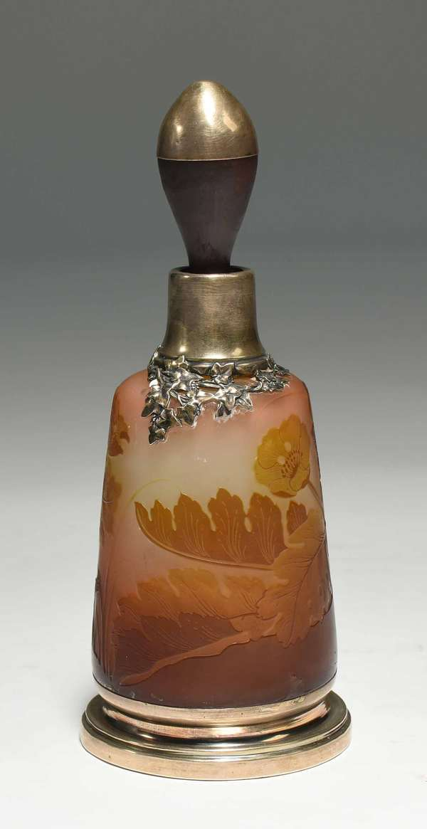 "Gallé cameo glass and silver mounted perfume bottle with poppy decoration in yellow, pink and orange colored glass. With silver mount at rim in a grape vine motif. 8.25""H x 3.25"" dia. 1 lb. Condition: silver mounts have most likely been reglued. Small chip to shoulder."