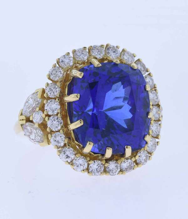 Stunning eighteen karat (tested) yellow gold ring set with an approximate 15.5 ct. tanzanite with dark bluish violet color, very very slightly included (very minor chip and scratch) accented by 2.0 ct. tw. round brilliant and marquise cut diamonds, G-H color, VS clarity, very good cut. Ring size 5 ½. 11.9 grams. Excellent condition.