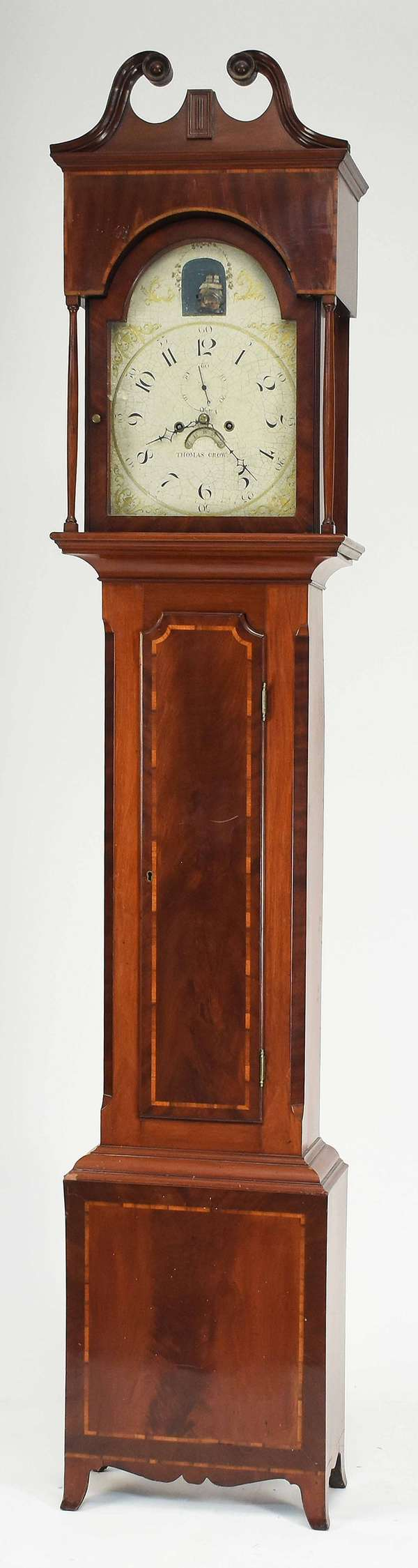 "Thomas Crow, Wilmington Delaware, Federal mahogany grandfather clock, case with banded inlay on French feet, bonnet flanked by slender side columns. Dial signed ""Thomas Crow"", hand painted with gilding and rocking ship movement. 97""H, bonnet 19.5""W x 10""D. Condition: glass in bonnet cracked in lower right corner, bonnet with some old repairs but mainly original. Base appears mostly original some old repairs. Craquelure to dial but original paint."