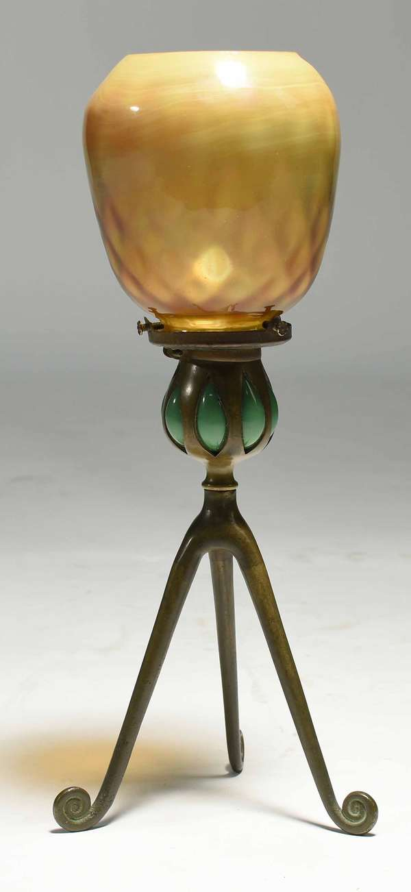 "Tiffany Studios bronze tri-footed candlestick lamp, with green glass decoration, inscribed on rim ""Pat'd Dec 9, 90, Sept 29, 96,"" inscribed on underside of foot, ""D441."" Yellow/gold favrile shade, signed on bottom ""L.C.T."" Shade: 4.25""H x 4"" dia. Base: 8.25""H. Overall: 12.5""H. 1.5 lbs. Condition: a few minuscule chips to underside of shade where it connects to base."