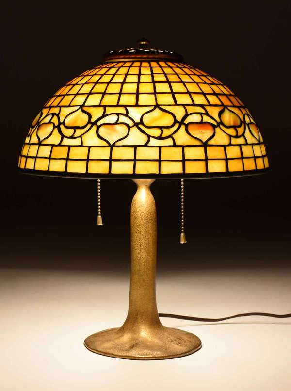 "Tiffany lamp on doré bronze flared base, 13.5""H, stamped on underside ""Tiffany Studios, New York, 551,"" with an olive and gold leaded glass shade in acorn motif, signed on bottom rim ""Tiffany Studios New York, 1410."" 12"" dia., 5""H. Lamp overall 15""H. 8 lbs. Condition: one small pane cracked near top, chipping to interior edges of four acorns, not visible from front."
