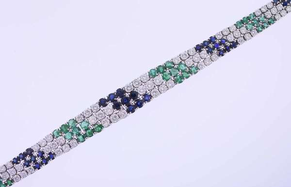 Triple row eighteen karat white gold line bracelet set with approximately 12 ct. tw. round brilliant cut diamonds, G-H color, VS-SI clarity, very good cut, 3.0 ct. tw. round brilliant cut emeralds with medium slightly bluish green color (included-slightly included, slightly abraded, minor chips) and 5.0 ct. tw. round brilliant cut dark slightly violetish blue sapphires. It measures ½ inch wide by 5/16 inches at the ends and is 7 3/8 inches long. 44.1 grams. Very good condition.
