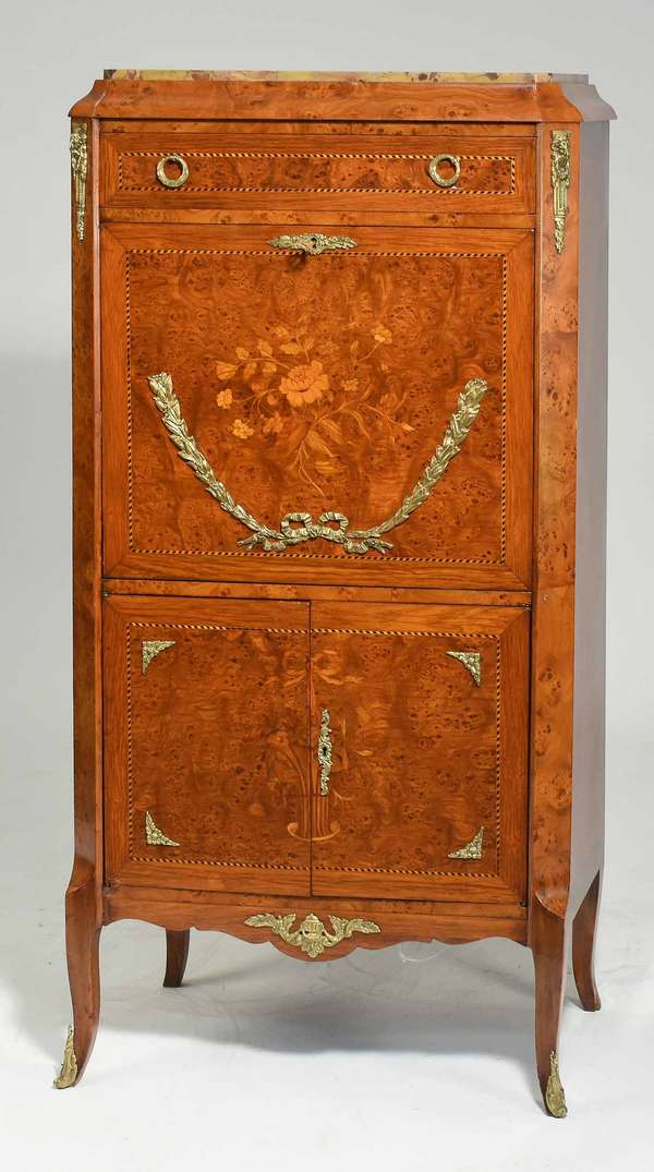 "Small French secrétaire abbatant, with burl wood panels inset with floral marquetry. With ormolu mounts in rams head and Classical swag motifs. Marble top. Top drawer, with drop down panel below revealing a writing surface and fitted interior with marquetry panels. Two doors below. On delicate French feet, ca. 1920. 55""H x 26.5""W x 15""D. Condition: Nick to top edge, see photos. Marble with old repair to front left corner, chip to back edge."