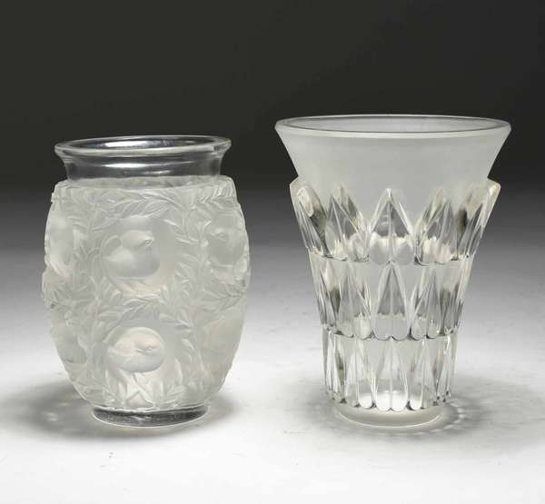 "Two Lalique vases, ""Feuilles"" vase, geometric leaves, 7""H x 5.5"" dia.; and ""Bagatelle"" vase, with birds in trees, 6.5""H x 4.25"" dia. Both signed on underneath. 7.5 lbs total. Condition: few very small chips to bottom of ""Bagatelle."" Scuffing to bottoms of both."