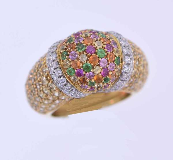 Dome topped eighteen karat yellow gold ring pave set with approximately 3.0 ct. tw. light yellow, bright orange, light and bright pink sapphires, accented by several medium dark green tsavorite garnets, one emerald, and two brown diamonds, approximately 1.0 ct. tw. and .60 ct. tw. round brilliant cut colorless diamonds, G-H color, SI-I1. Ring size 5 ½. 12.3 grams. Very good condition.