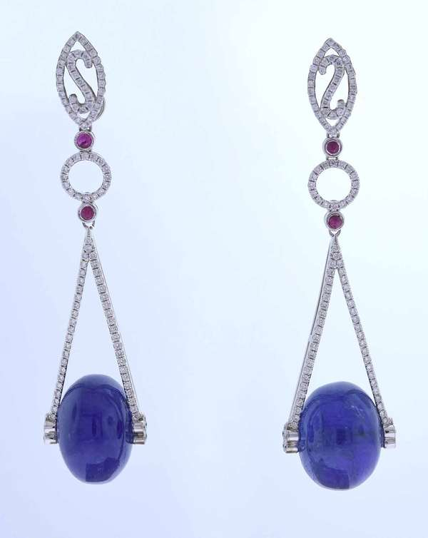 Eighteen karat white gold drop earrings with posts featuring 16 mm round spherical medium blue sapphire beads (inclusions), approximately 50 ct. tw. accented by 1.15 ct. tw. round brilliant cut diamonds, H color, SI clarity, very good cut. There are also four, 2 mm round medium dark slightly purplish red ruby cabochons, approximately .15 ct. tw. 2 ½ inches long. 19.1 grams. Like new condition.