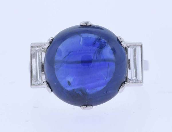 Striking platinum (tested) ring with beautiful hand pierced scrolled undercarriage set with an approximately 10 ct. round dark slightly violetish blue sapphire cabochon (large feather from table to girdle only visible tilted at certain angles), accented by .60 ct. tw. baguette diamonds, I color, VS-VVS clarity. Ring size 4 ¾. 6.6 grams. Very good condition.