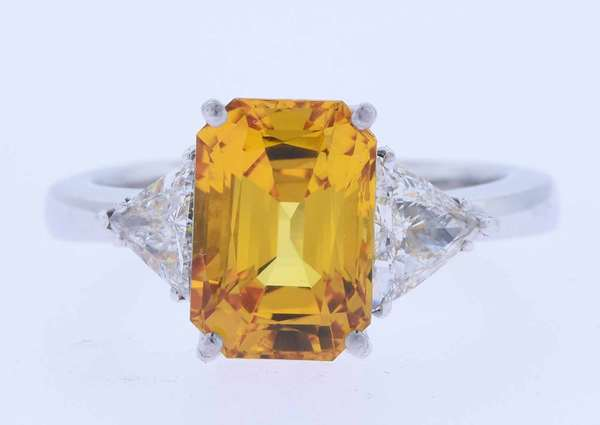 Eighteen karat white gold ring set with an approximate 6.0 ct. radiant cut, strongly orangish yellow sapphire, eye clean, enhanced by two brilliant cut triangular diamonds, approximately 1.2 ct. tw., H-I color, VS-SI clarity. Signed Zydo, sold at Neiman Marcus. Ring size 9 ½. 9.5 grams. Very good condition.