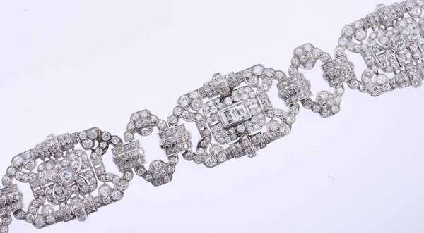 Stunning Edwardian platinum and diamond bracelet set with two larger Old European cut diamonds, approximately 1.50 ct. tw., I-J color, SI clarity, good cut, as well as two emerald cut diamonds set in the center, 1.30 ct. tw., J-L color, SI-I1 clarity, accented by approximately 18 ct. tw. Old European cut and single cut diamonds, H-J color, VS-SI clarity (minor chips). It measures 1 ¼ inch wide and is 7 ½ inches long. Safety chain. 73.4 grams. Very good condition.