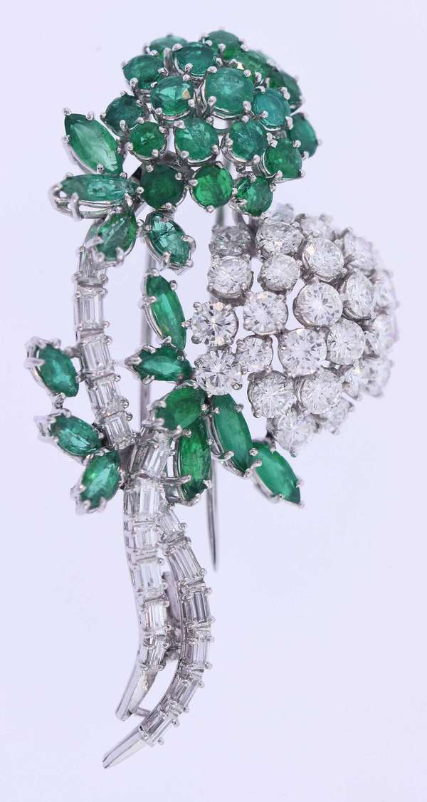 Emerald and diamond floral motif pin in eighteen karat white gold set with approximately 2.5 ct. tw. round brilliant and marquise cut, medium slightly bluish green emeralds as well as 4.5 ct. tw. round brilliant and baguette cut diamonds, G-H color, VS clarity, very good cut. It measures 2 inches long by 1 ½ inches wide. 15.8 grams. Condition: very good