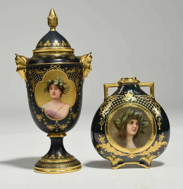 "Two pieces of Royal Vienna porcelain, lidded urn with portrait of ""Daphne"" in quatrefoil cartouche, signed Wagner, on a dark green ground with gilding, flanked by gilded mask handles. Signed with beehive mark and titled on bottom. 11""H.; along with a round handled vase, with portrait plaque of ""Medora"" on dark green ground, with gilded decoration. Signed with blue beehive mark and titled on bottom. 6.25""H. 1.7 lbs total. Condition: some tarnishing to gilding on ""Daphne"", chipping to gilding where it attaches to base. Some wear to gilding on neck and rim of ""Medora."""