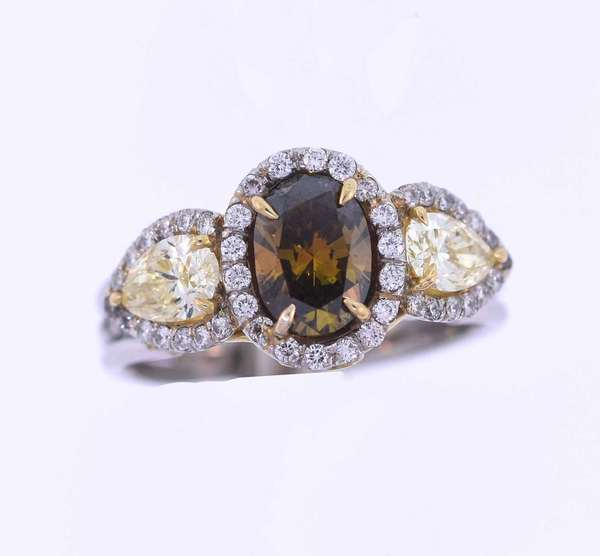 Platinum and diamond three stone halo style ring set with approximately 1.70 ct. oval diamond with a dark slightly orangish brown with a yellowish green modifier, SI clarity, good cut, accented by two medium – medium light yellow pear shape diamonds, 1.0 ct. tw., very good cut, VS clarity, accented by .25 ct. tw. colorless round brilliant cut diamonds, F-G color, VS clarity, excellent cut. Ring size 7 ¼. 8.2 grams. Condition: very good