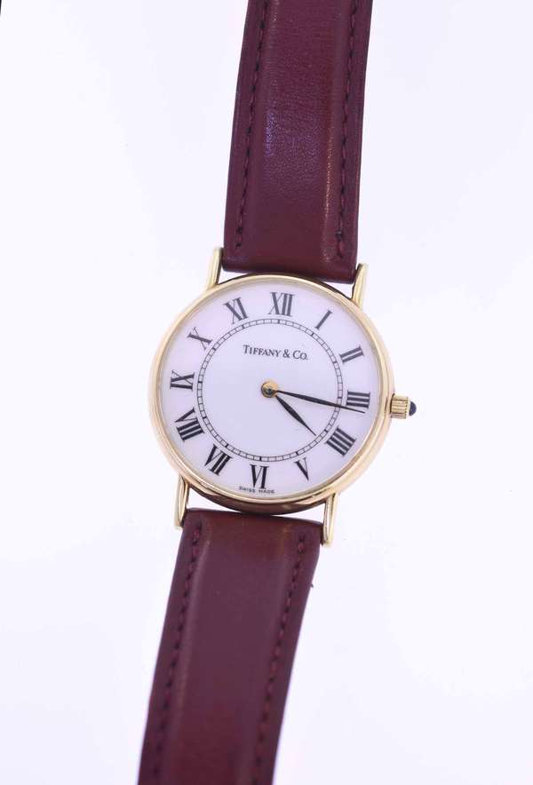 "Men's 14K gold Tiffany and Co. wrist watch, yellow gold housing with white dial signed Tiffany and Co. burgundy brown leather strap, with the Tiffany logo on the clasp, approx. 8.5""L, dia. of watch 1.25"". Condition, generally very well lightly used, some wear to band, crystal good, likely needs at battery."