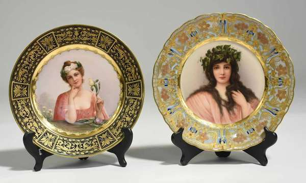 "Two 19th C. Royal Vienna cabinet plates; beauty with dark hair and ivy wreath, ""Epheu,"" with border of gilding and flower motif, signed Wagner. Signed on bottom with beehive mark, and titled ""Epheu."" 10"" dia. Other example with center plaque of woman in pink with flower wreath, ""Iris"", with a cobalt and gold border, signed Wagner. Bottom signed with beehive mark and titles ""Iris."" 9.75"" dia. 2 lbs. Condition: some scratching to gilding. Three minuscule chips to glaze on woman with flowers."