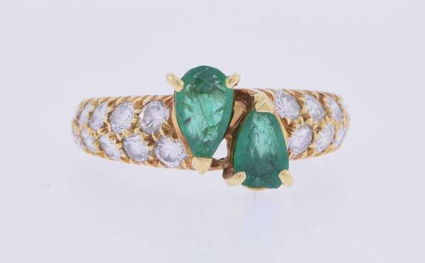 Van Cleef and Arpels (signed, 6-24-71) eighteen karat yellow gold ring set with approximately .50 ct. tw. medium – medium dark slightly bluish green, slightly – moderately included pear shape emeralds (slightly abraded), accented by .75 ct. tw. round brilliant cut diamonds, F-G color, VS clarity, excellent cut. Ring size 4 ½. 4.0 grams. Good condition.