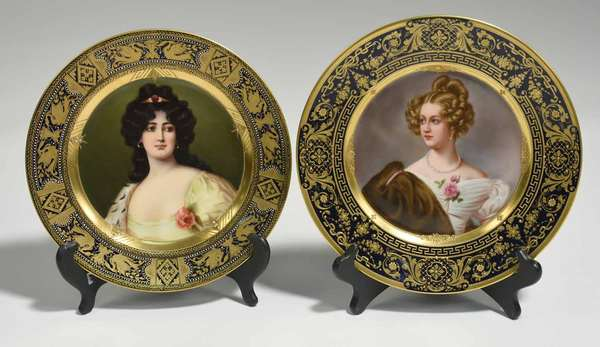 "Two Royal Vienna cabinet plates, portrait of woman in furs, ""Amalie v. Krudener,"" with a cobalt and gold border, stamped on back CMHR. 10"" dia. With other, woman in yellow with dark hair, ""Tida."" With cobalt and gilded border in swan and urn motif. Signed with blue beehive mark. 9.5"" dia. 2.2 lbs total. Condition: 3 gold balls missing from inner gilding of ""Tida."""