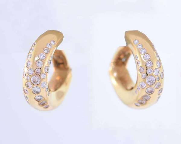 Chaumet (French, signed) huggie style hoop post earrings in eighteen karat yellow gold set with approximately .80 ct. tw. round brilliant cut diamonds, G color, VS clarity, very good cut. 14.1 grams. Condition: good