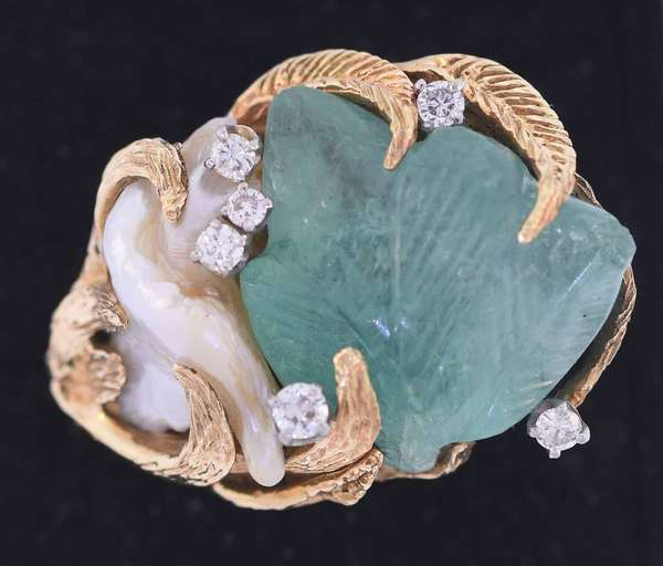 Fourteen karat yellow gold ring with leaf motif set with an approximately 10 ct. very light green carved leaf emerald set alongside a freshwater pearl, accented by .31 ct. tw. round brilliant cut diamonds, G-H-I color, VS-SI clarity, very good cut. Top profile measures 1 ½ inches. 23.7 grams. Condition: very good