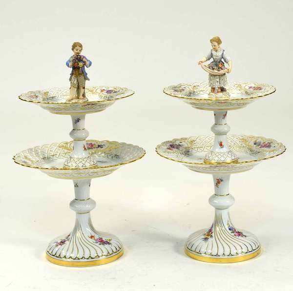 "Pair of Meissen two-tiered cake stands with figural finials, boy and girl. With reticulated platters, gilding and floral hand painted decoration, with crossed swords mark on underneath. 15.5""H x 9.5"" Dia. Condition: losses to delicate lace decoration on both costumes, losses to flower petals in boy's wreath. No other chips or cracks."