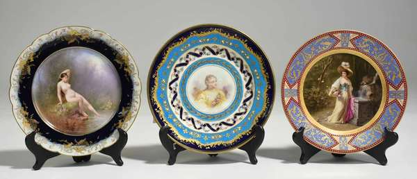 "Three cabinet plates, by Sèvres, Royal Vienna and Limoges. Sèvres example with cobalt, bleu céleste and gilded floral borders with hand painted center of woman in yellow with roses, 9.5"" dia. Crossed L's on bottom. Royal Vienna example with gilded, red and purple border with center hand painted of woman by a well, signed B. Rudolf, with beehive mark on bottom. 8.75"" dia. Limoges example with cobalt and gilt border, with center painted plaque of nude by river, signed Cadillou, stamped on bottom ""Limoges, J. Pouyat"". 9.5"" dia. 2.7 lbs total. Condition: Sévres example missing seven red dots around center. Some scratching to center image, very light scratching/wear to gilding on others."