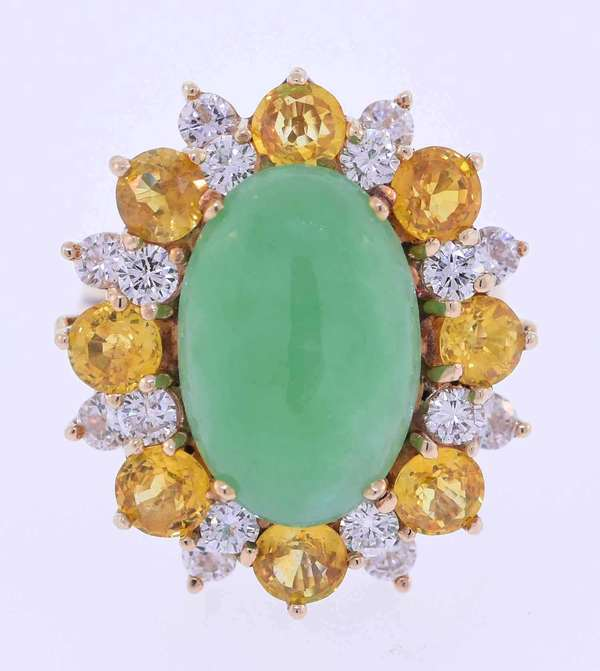 Fourteen karat yellow gold oval jade cabochon ring, jade is approximately 6.6 ct., semi-translucent, slightly mottled, very light green color surrounded by approximately 1.0 ct. tw. medium light yellow sapphire and 1.0 ct. tw. round brilliant cut diamonds, G-H color, VS clarity, very good cut. Ring size 6 ¾. 8.9 grams. Very good condition.