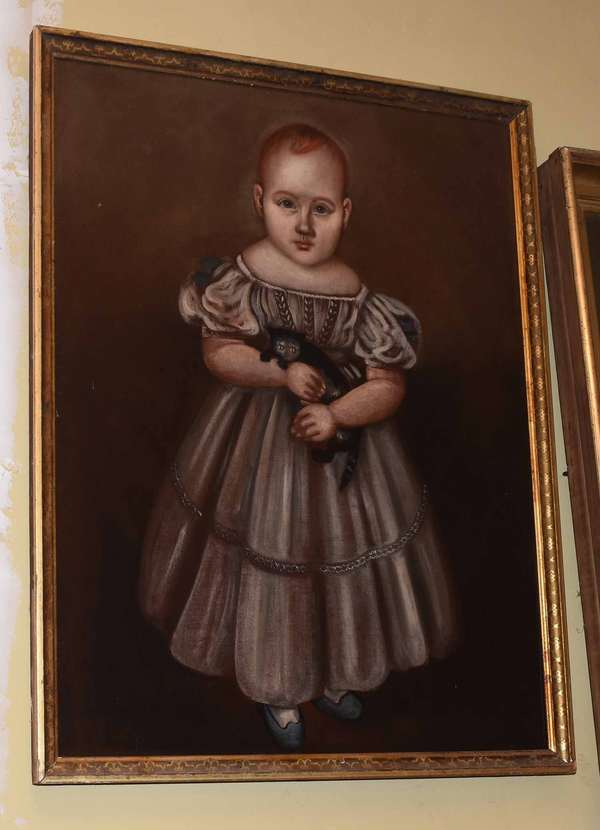 "19th C. American school folk portrait oil on canvas, child with red hair in dress holding a black cat, stretcher 28"" x 23"", overall 24.5"" x 29.5"". Condition: relined on metal, evidence of inpainting in right side of background under blacklight."