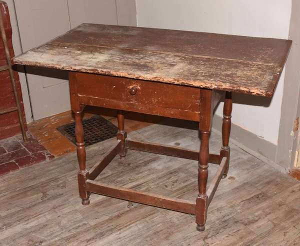 "18th C. New England tavern table with a single-board breadboard end top, one drawer, on turned legs with a square stretcher base. 27""H. x 40""L x 24.5""W. Condition: top with finish losses, shrinkage crack to top, loss to one foot, overall wear."