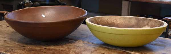 "Two wooden chopping bowls in paint: mustard painted bowl, 16.5"" - 17.5"" dia.; with a red painted bowl, 18""-19"" dia. Condition: expected wear in center of mustard bowl, also paint loss around base; brown bowl with a few minor nicks."
