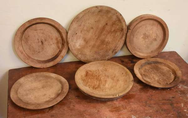 Six early treenware plates, in old natural finish. 7