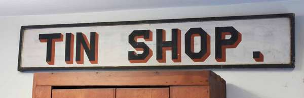 "19th C. painted trade sign ""Tin Shop"", in white, black and red paint, 66""L. x 11""H. Painted over earlier sign. Condition: minor loss in letters S and H, minor wear. Very slight warping to board"