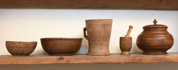 "Five pieces of early woodenware, including treenware covered pot, signed underneath lid ""Lydia L. Eastbrook, Newbury Ohio"", 4""H; handled cup, 4.25""H x 3.25"" dia.; small burl wood bowl, 3.5"" dia x 1.5""H; bowl 5"" dia.; with a miniature mortar and pestle, 3.5""H overall. Including a collection of 97 antique marbles. Condition: good and expected wear."