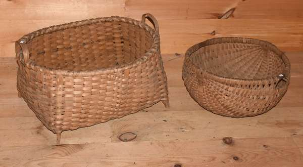 "Two baskets, rare footed example with handles, 25.5""L. x 15""H. with a harvest basket, 21""L x 10.5""H. Condition: footed with water staining and some damage at one corner."
