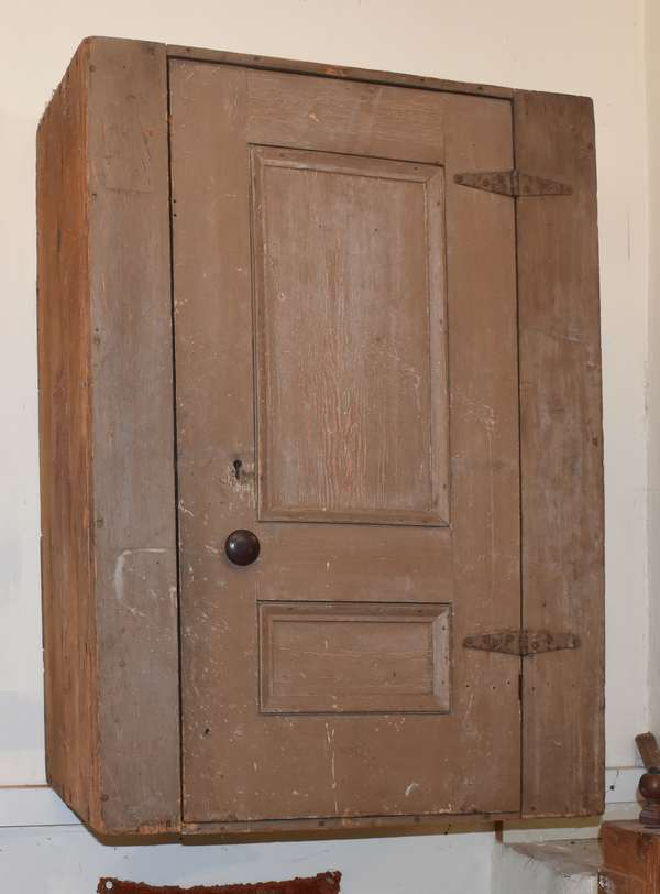"19th C. hanging cupboard, with single paneled door in old brown paint, interior shelves and two drawers. 24""W. x 34""H. x 13""D. Condition: expected abrasions and light paint wear"