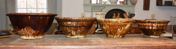 "Four Bennington style pottery bowls,  9"", 10.25"", 10.25"", and 12"" dia. Condition: overall scuffing, craquelure to insides, chip to bottom of mid-sized bowl."