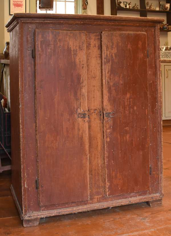 18th C. country two-door jelly cupboard in old red paint with molded top, two blind doors on a bracket base, 38