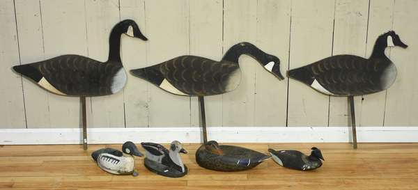 "Three painted paperboard goose decoys 33""L., with two wooden duck decoys, one with moving head, 13""L and 14""L, and two other duck decoys, one signed H. Wittington Oglesby, Ill., Oct. 1963 16""L, with an older decoy with weight, 14""L. Condition: light paint wear present on all, cracking to Oglesby example"