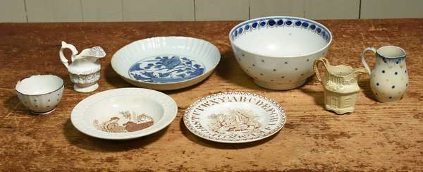 "Eight pieces of semi-porcelain and pearlware, including Staffordshire ABC plate, 6.75"" dia, bowl with blue interior decoration, 7.25"" dia. x 3.5""H, three pitchers, 3.25"" - 3.5""H, cup 3.25"" dia., and two plates, 6.75"", 8"" dia. Condition: chipping to foot of bowl, rim and foot of cup, craquelure throughout."