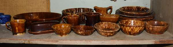 Twenty pieces of Bennington style pottery including cake mold, butter dish, plates, mugs, wash basin, pitcher, etc. Condition: scuffing throughout, heavy chipping to edge of one plate.